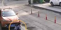 Woman On The Phone Crouching In Front Of An Suv Gets Knocked Down