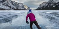 Adventurous Woman Ice Skating On Frozen Lake In Canada