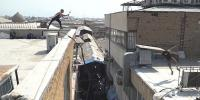 Man Changes Clothes While Hanging Off The Side Of Buildings In Tehran To Honour Father