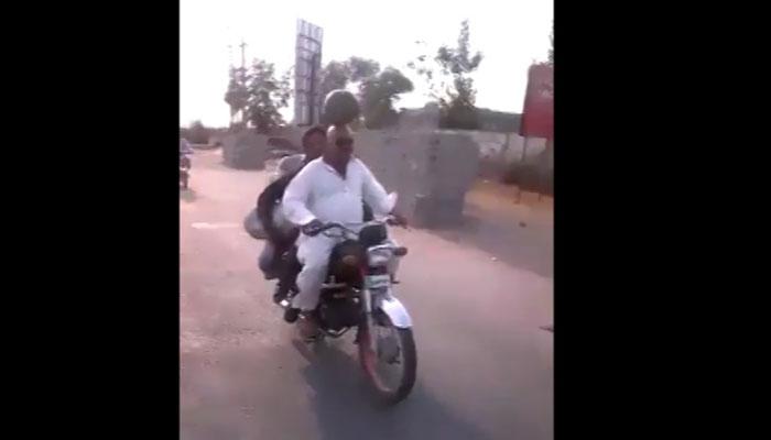 سرپر بھاری تربوز رکھ کر موٹرسائیکل چلانے کا مظاہرہ
