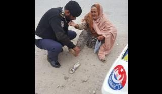 Young Police Officer Helping Old Woman